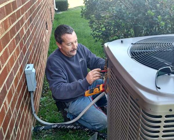 Richmond HVAC Service tech repairing heat pump unit